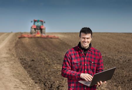 gente exitosa: agricultor joven con ordenador portátil supervisar el trabajo en las tierras agrícolas, tractores desgarradora en el fondo Foto de archivo