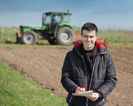 harrowing: Young farmer supervising work and writing notes on farmland, tractor harrowing in background Stock Photo