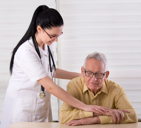 ambulant: Young pretty nurse holding her hands on the shoulder and hands of old man and smiling. Concept of senior people care