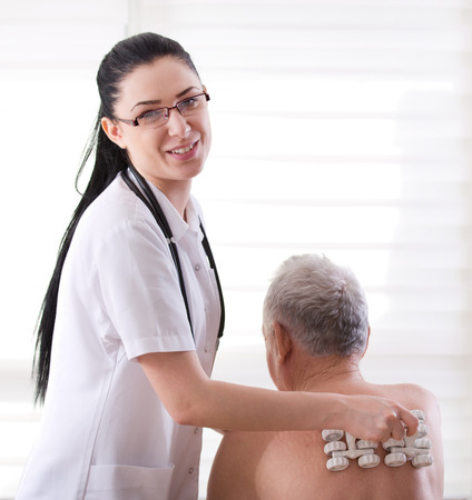 old man on a physical pressure: Young pretty practitioner massaging senior man with plastic roller massager Stock Photo