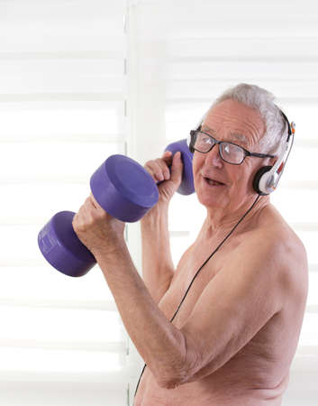 eighties: Senior man in his eighties training with dumbbells and listening to the music Stock Photo