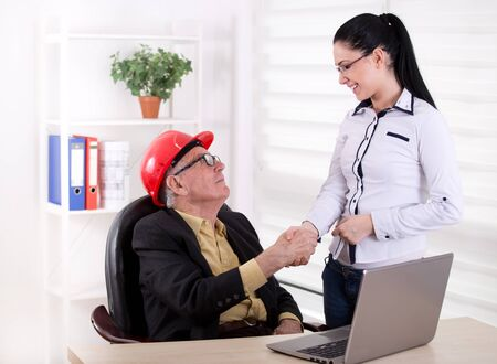assistant engineer: Senior engineer with helmet shaking hands with young female assistant in the office Stock Photo