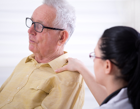 Portrait of senior man with young nurse holding her hand on his shoulder. Senior care concept