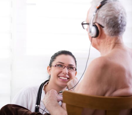 sound therapist: Smiling young nurse taking care about senior man with headset