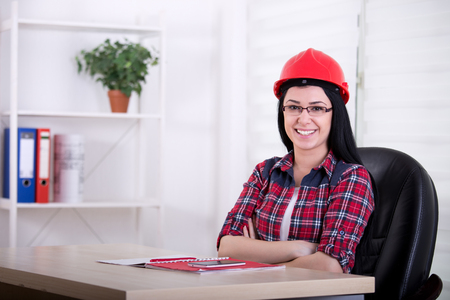 casco rojo: Confident young woman engineer with red helmet sitting at desk in the office