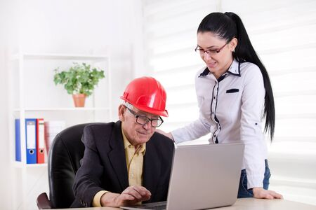 assistant engineer: Senior engineer with helmet and young female assistant looking at laptop in the office Stock Photo