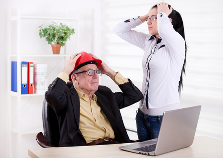 raised arms: Senior engineer and young assistant having big problem on the project. Both holding head with raised arms in the office Stock Photo