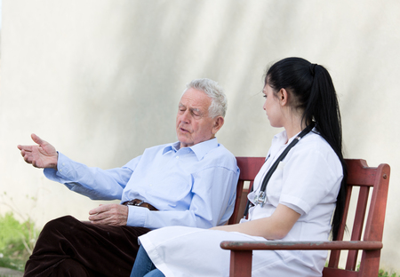 outpatient: Senior man talking to young nurse on the bench. Senior care concept