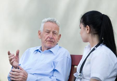 Senior man talking to young nurse on the bench. Senior care concept