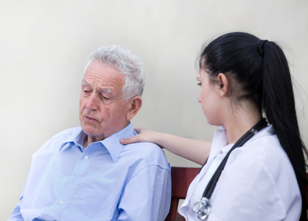 outpatient: Young woman caregiver listening and comforting senior man on the bench Stock Photo