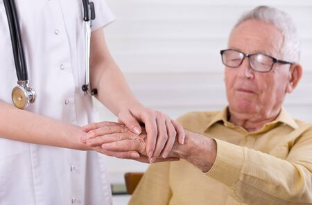 ambulant: Close up of young nurse hands holding hands of old man. Senior care concept