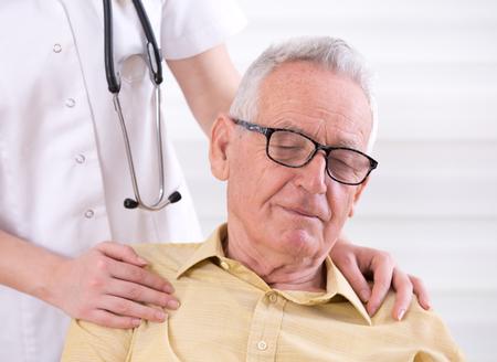 ambulant: Senior care concept. Young nurse holding hands on shoulders of old smiling man
