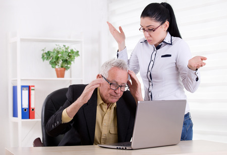 raised arms: Senior man and young woman having problem in the office. Both holding head with raised arms