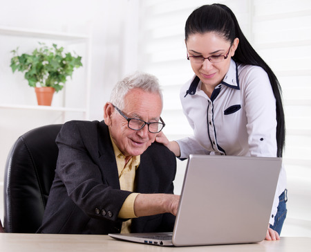 familiy: Senior man and young woman smiling and looking at laptop in the office Stock Photo