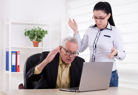 holding on head: Senior man and young woman having problem in the office. Both holding head with raised arms