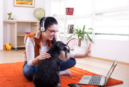 Girl with dog sitting on the floor in the room and talking on video call on laptop