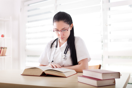 Young girl, student of medicine studying and researching books at desk in the office