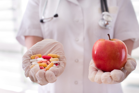 hand holding pills: Female doctor holding pile of pills in one and fresh red apple in other hand Stock Photo