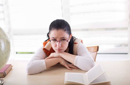 conceived: Young pretty student girl leaning at desk with books in front of her and having conceived expression on face