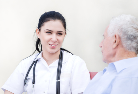 outpatient: Young pretty nurse explaining something to senior man on the bench in courtyard