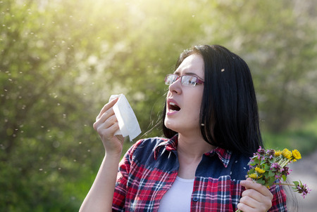 ambrosia: Young girl sneezing and holding paper tissue in one hand and flower bouquet in other. Allergies concept Stock Photo