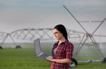 agronomist: Young woman agronomist standing on field with laptop. Water irrigation system in background