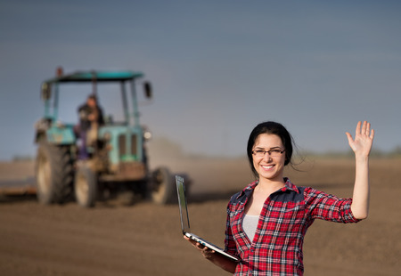 harrowing: Young happy farmer girl standing on field with laptop in spring time. Tractor working in background Stock Photo
