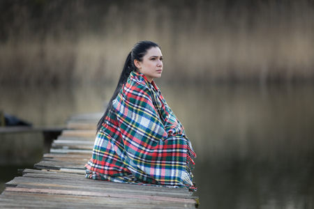 conceived: Pretty young woman covered with blanket sitting on wooden dock on the river