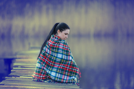 wooden dock: Pretty young woman covered with blanket sitting on wooden dock on the river