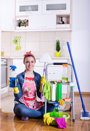 cleaning supplies: Happy beautiful young woman sitting on the kitchen floor with cleaning supplies on ladder