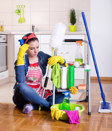 cleaning supplies: Tired beautiful young woman sitting on the kitchen floor with cleaning supplies on ladder and feeling bored