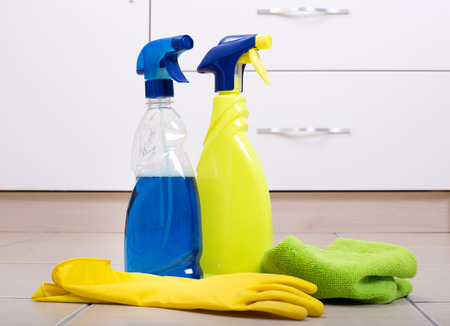 floor cloth: Two spray bottle with rubber protective gloves and green cloth on the tiled floor in the kitchen