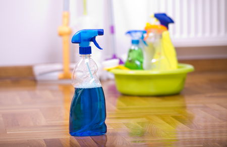household objects equipment: Close up of spray bottle for floor cleaning with different cleaning supplies and equipment in background