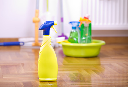keeping room: Close up of spray bottle for floor cleaning with different cleaning supplies and equipment in background
