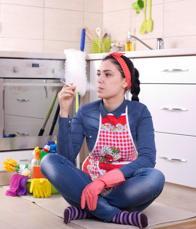 Young pretty cleaning lady sitting on the floor in the kitchen and smoking cigarette Stock Photo
