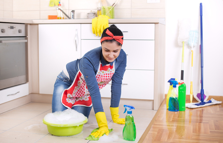 floor cloth: Young pretty woman cleaning kitchen floor with cloth and foam from basin