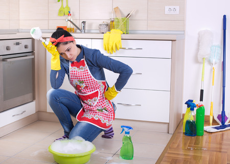 Unhappy young cleaning lady holding head with hand and squating in front of cleaning supplies and equipment