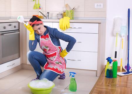 Unglückliche junge Putzfrau hält den Kopf mit der Hand und squating vor Reinigungsmaterial und Ausrüstung Standard-Bild - 57944603