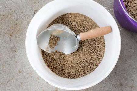 Bovenaanzicht van pellets voor vee in de emmer met spade voor het doseren op de boerderij. Gezonde koe voeden