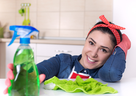 spray bottle: Smiling young cleaning lady with pink rubber gloves holding spray bottle in the kitchen