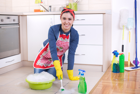 Satisfied woman scrubbing tiled floor with brush in kitchen and looking at camera
