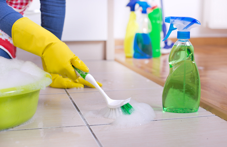 scrubbing up: Close up of female hands with protective rubber gloves scrubbing kitchen floor with brush Stock Photo