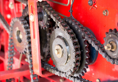 agricultural engineering: Gear wheels in agricultural machinery. Complexity of chains and gears on red background
