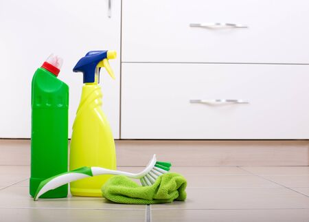 Close up of two bottles of cleaning detergent with cloth and brush on kitchen floor and kitchen cabinets in background Stock Photo