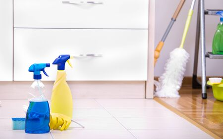 cleaning services: Cleaning supplies and equipment on the tiled floor in the kitchen