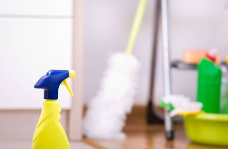 kitchen cabinets: Close up of spray bottle in front of kitchen cabinets and other cleaning supplies and tools in background