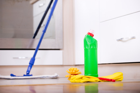 cleaning services: Close up of bottle with disinfectant, protective gloves and brush on kitchen floor and oven in background. House cleaning concept