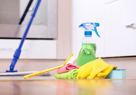 Reiniging van benodigdheden en uitrusting op de keukenvloer met oven op de achtergrond
