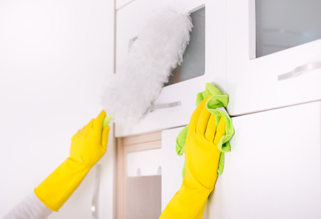kitchen cabinets: Close up of human hands cleaning and dusting kitchen cabinets Stock Photo
