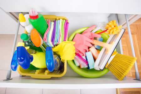 Top view of cleaning supplies and equipment stored in drawer in kitchen cabinet. House cleaning and storing concept